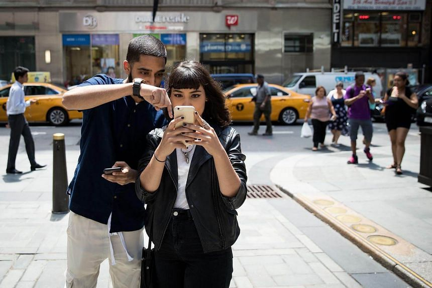 People playing Pokemon Go on their smartphones outside of Nintendo's flagship store on July 11, 2016 in New York City.