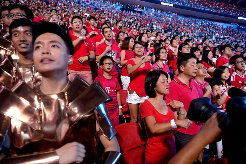 Spectators and performers perform national day songs using sign language during NDP 2016 at Singapore Sports Hub on August 9.