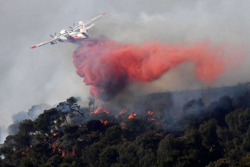 A plane sprays fire extinguisher as part of an attempt to struggle against a fire which has already devastated some 200 hectares in Vitrolles, southern France on Aug 10, 2016.