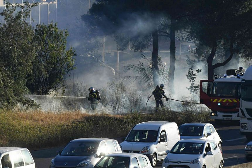 Motorists drive on the highway next to firefighters spraying fire extinguisher as part of an attempt to struggle against a fire that spread near Vitrolles, southern France on Aug 10, 2016.