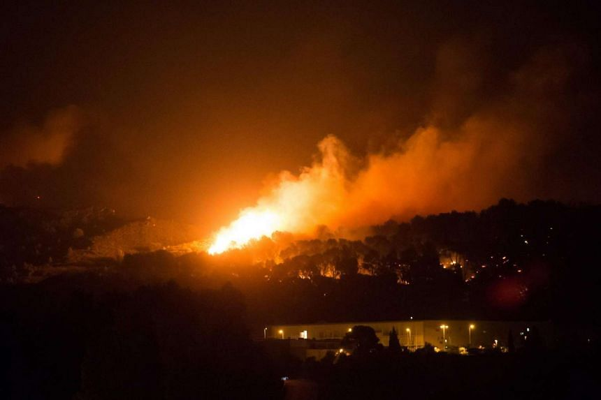 A fire spreads above the highway in Vitrolles, southern France, on Aug 10, 2016.