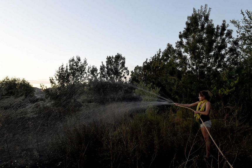 A girl waters her garden to prevent the fire fro spreading at Les Vitrolles, near Marseille, southern France on Aug 11, 2016.