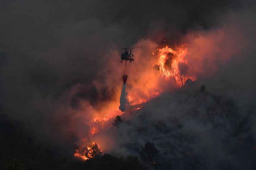 An helicopter carries an extinguisher in the struggle against a fire that spread near Vitrolles, southern France on Aug 10, 2016.