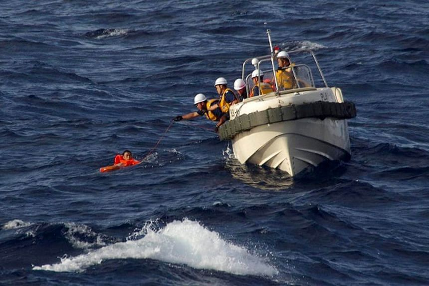Japan Coast Guard rescue workers reaching out to the crew of a Chinese fishing boat that sunk following a collision with a Greek cargo vessel in the Senkaku (or Diaoyutai) Islands, Japanese southwestern islands.