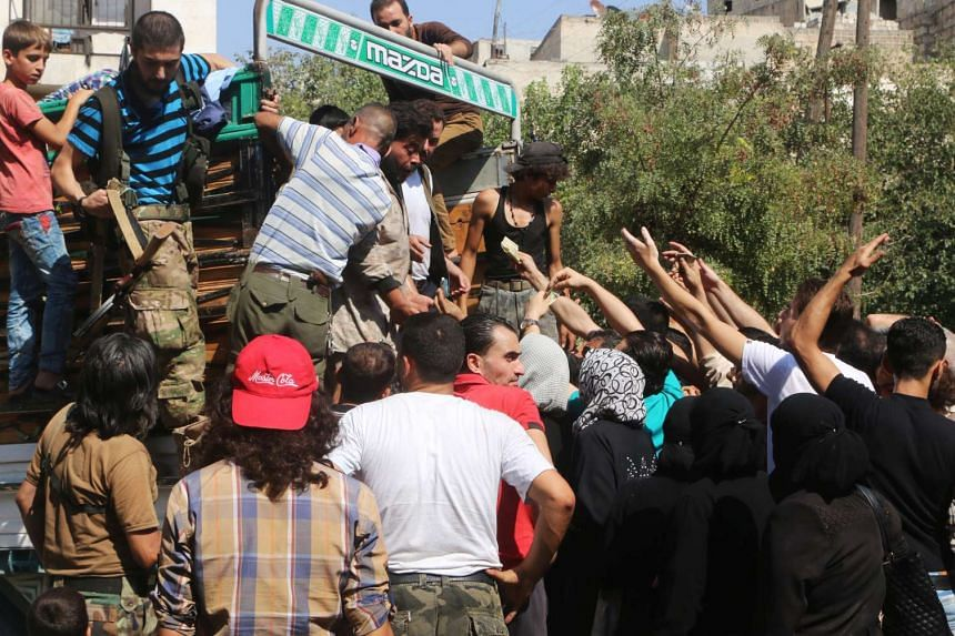 People gather to buy fresh produce that was brought into rebel held areas of Aleppo by private traders, on Aug 11, 2016.