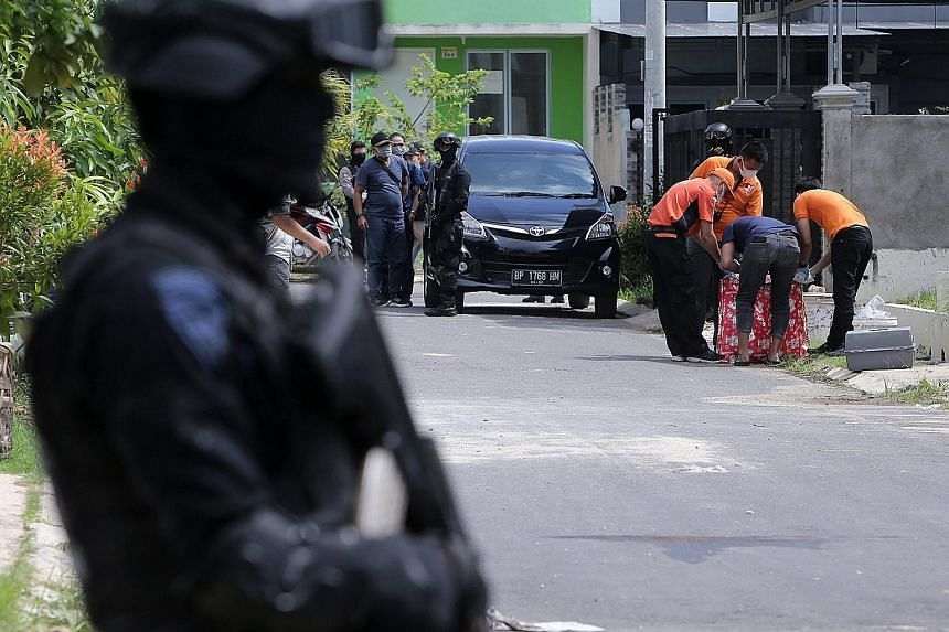 Indonesian anti-terror police searching for evidence during a raid at a residential area in Batam last Friday. Six people were arrested on the island last week. The cell leader had planned to fire a rocket at Singapore's Marina Bay.