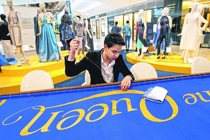 """A Thai well-wisher using golden thread to embroider """"Long Live the Queen"""" on a 7m-long silk banner, ahead of Queen Sirikit's birthday preparations yesterday in Bangkok. Thailand's popular Queen Sirikit will turn 84 tomorrow."""