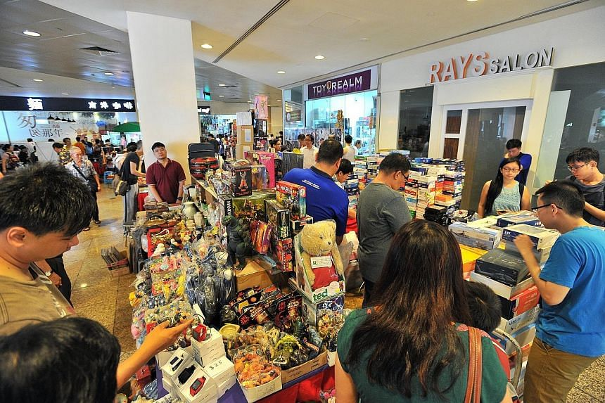 People checking out the toys, collectibles and antiques on sale at the flea market in China Square Central on Sunday. Mr Michael Poh, the organiser of the mall's popular flea market for the past 11 years, says there has been no official word on wheth