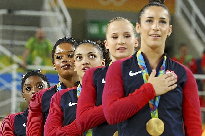 While Simone Biles wobbles slightly on the beam (top), she still nailed a team-high 15.300, and her brilliant performances gave the United States team - (above from right) Aly Raisman, Madison Kocian, Laurie Hernandez, Gabby Douglas and Biles - a com