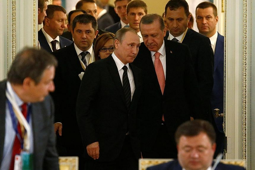 Russian President Putin (front, in black tie) and Turkish President Erdogan (in pink tie) at a meeting with businessmen in St Petersburg, Russia, on Monday. Russia is Turkey's second- largest trading partner after Germany.