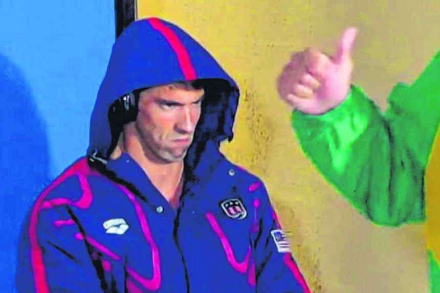 Michael Phelps' focus on winning was caught on camera on Monday before his 200m butterfly semi-final race (top). The American's facial expression was an instant hit on the Internet, with some fans producing memes that likened his intense stare to tha