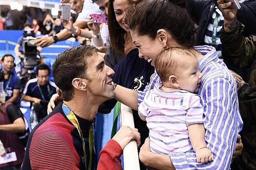 """Michael Phelps getting acquainted with his gold medal from his """"bread and butter"""" 200m fly event before approaching the spectator stands (above) to celebrate with his partner Nicole Johnson and son Boomer."""