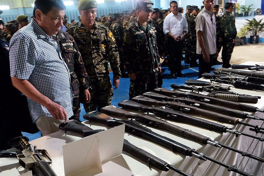 Mr Duterte inspecting confiscated firearms at a military camp in the southern Philippines on Tuesday. The President, who has been touring army camps since taking office five weeks ago, said he planned to recruit 20,000 more soldiers to help protect t