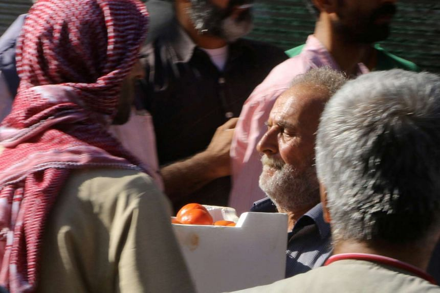 A man carries a box of tomatoes he received as food aid in Aleppo, Syria, Aug 10, 2016.