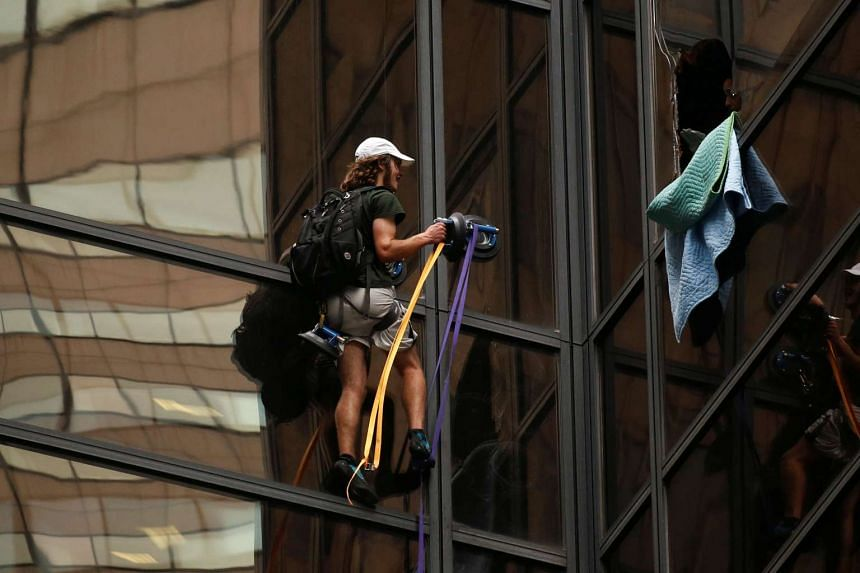 Officers from the NYPD watch the man scale Trump Tower.