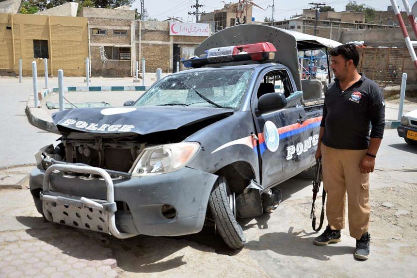 A Pakistani security official stands beside a damaged police vehicle after a bomb blast in Quetta, on Aug 11, 2016.