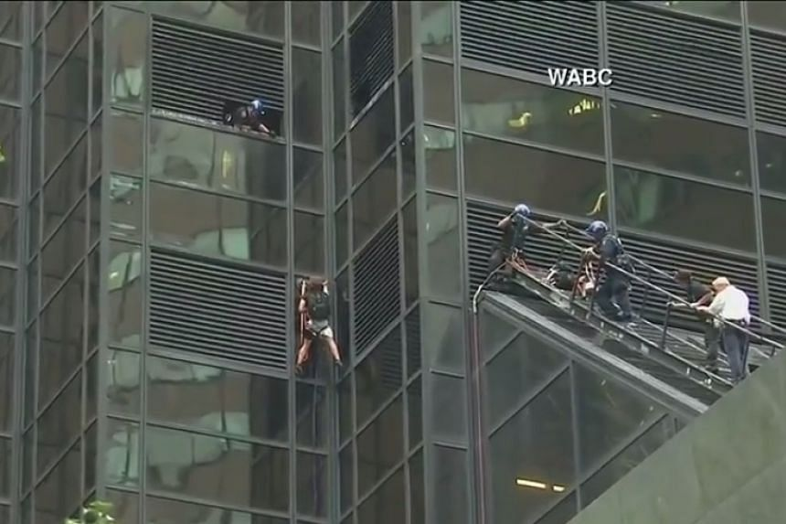 A screenshot from a live TV feed of the the man climbing Trump Tower.
