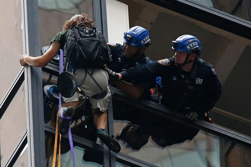 New York City Police grab Rogata on the 21st storey of Trump Tower and pull him to safety.