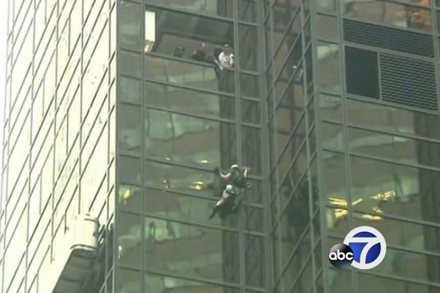 Police officers remove windows in an attempt to catch the climber.