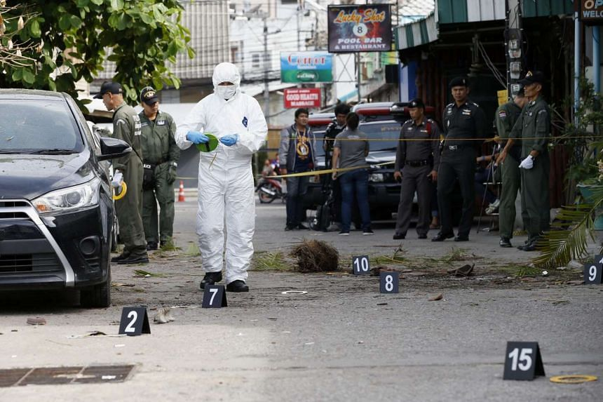 Thai forensic police officers inspect a scene where a bomb exploded on late Aug 11, at a popular tourist area in Hua Hin, Thailand.