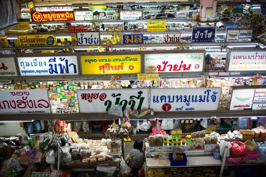 Rows of signs are displayed above stalls at Waworat Market in Chiang Mai, Thailand. The archetypical Thai consumer is deep in debt and borrowing against future income to fund basic consumption.