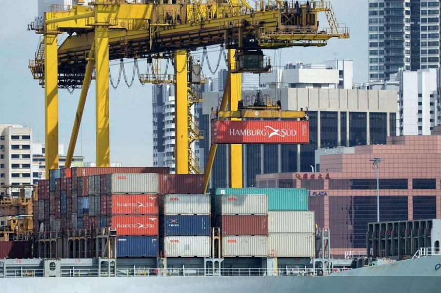 A container is loaded onto a ship docked at the terminal port in Singapore on June 17, 2016.