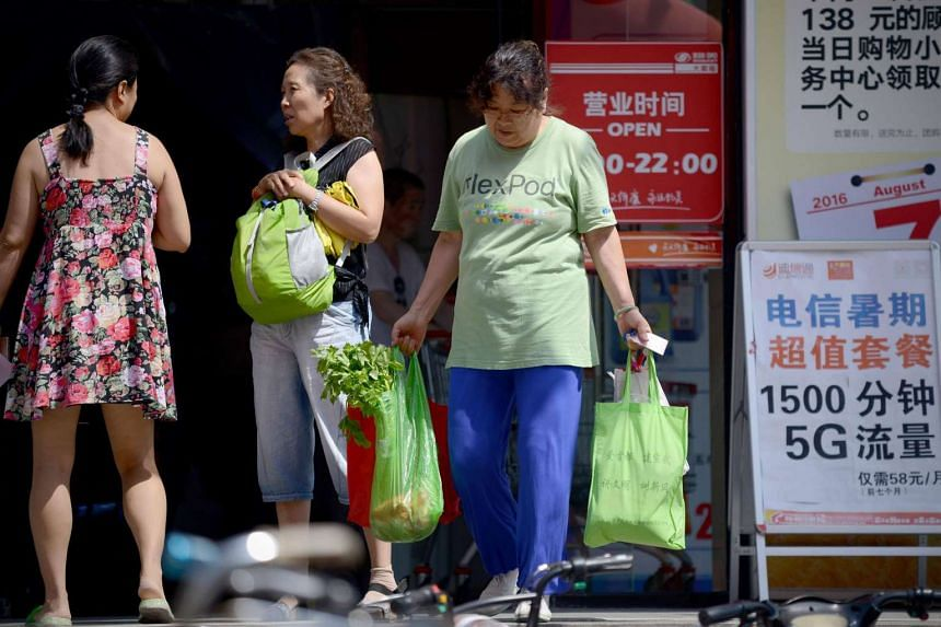 A woman walks out of a supermarket with a sack of vegetables in Beijing on Aug 9.