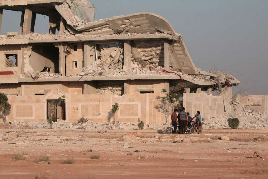 Residents stand near a damaged building in Manbij, in Aleppo Governorate, Syria on Aug 9, 2016.