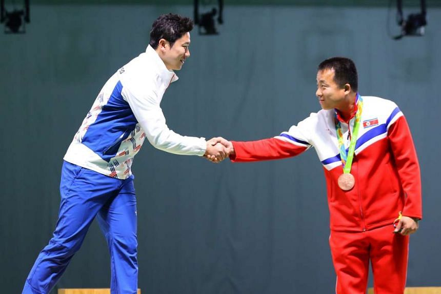 South Korea's Jin Jong Oh (L) shakes hands with North Korea's Kim Song Guk during the medal ceremony of the men's 50m pistol at the Rio 2016 Olympic Games at the Olympic Shooting Centre in Rio de Janeiro, Brazil, 10 August 2016. Mr Jin won the gold m