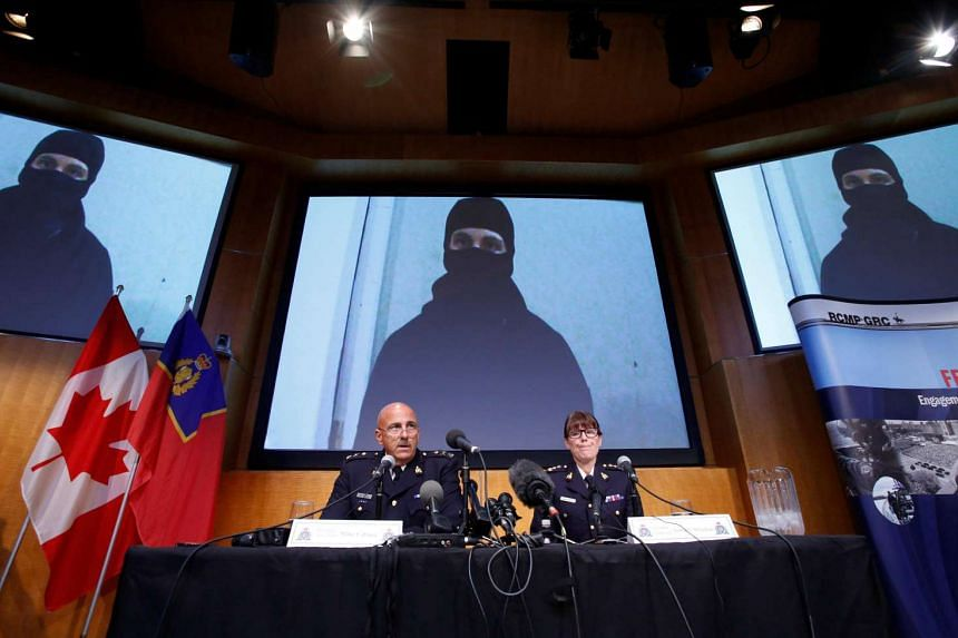 An image of Aaron Driver is projected on screens during a news conference with Royal Canadian Mounted Police (RCMP) Deputy Commissioner Mike Cabana (left) and Assistant Commissioner Jennifer Strachan in Ottawa, Ontario, Canada on Aug 11.