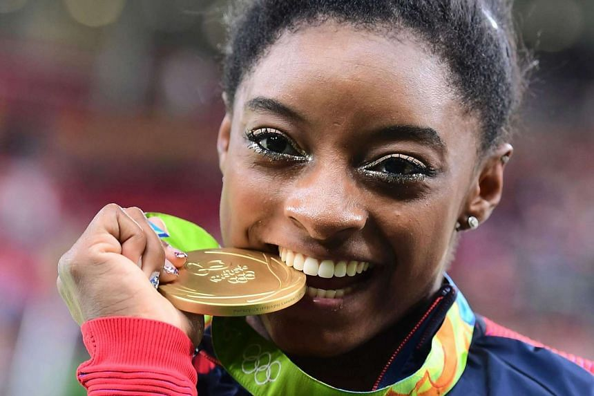 Simone Biles celebrates being crowned Olympic all around champion with a stupendous score of 15.933.