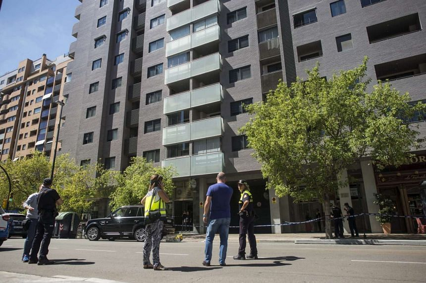 Spanish National Police agents stand at the spot where a man shot his ex-wife and then tried to commit suicide, in Zaragoza, Spain on Aug 12, 2016.