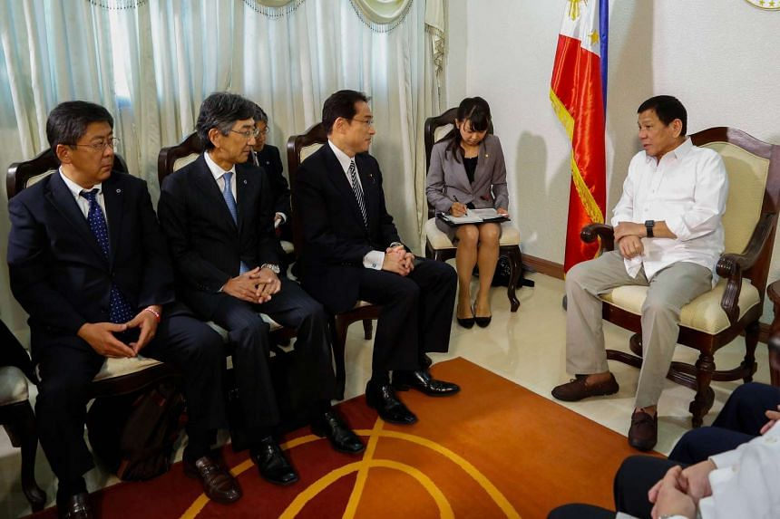 Philippine President Rodrigo Duterte (right) speaks with Japanese Foreign Minister Fumio Kishida (third from left) and his delegation at the presidential guest house in Davao city, Philippines.
