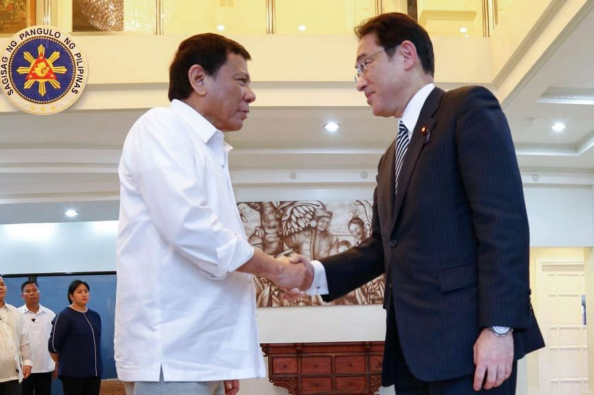 Philippine President Rodrigo Duterte (left) shakes hands with Japanese Foreign Minister Fumio Kishida during a courtesy call at the presidential guest house in Davao city on Aug 11, 2016.