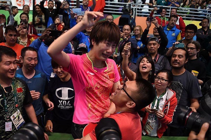 China's Ding Ning (in pink) celebrating with her supporters after beating compatriot Li Xiaoxia in their table tennis singles gold-medal match at the Riocentro venue on Wednesday. She had suffered a bitter loss to the same opponent in the London 2012