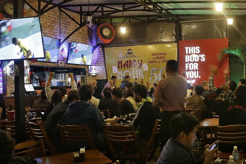 Above: Gabriel Barbosa scoring his second goal to round off Brazil's 4-0 thrashing of Denmark at Fonte Nova Stadium in Salvador. Both teams advanced to the knockout phase. Right: People watching the game on TV outdoors at a bar in Rio, dressed in jum