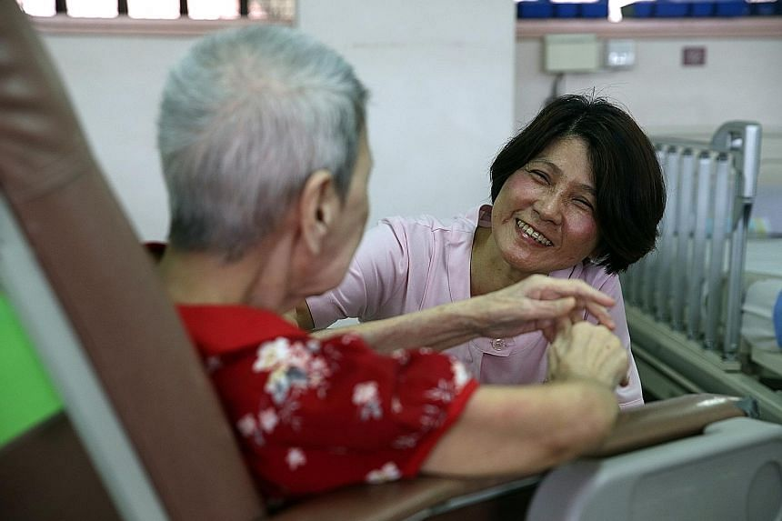 Staff nurse Lily Goh, 55, a former hospital nurse, talking to an elderly patient at Tai Pei Social Service. She left nursing for 15 years before making a comeback.