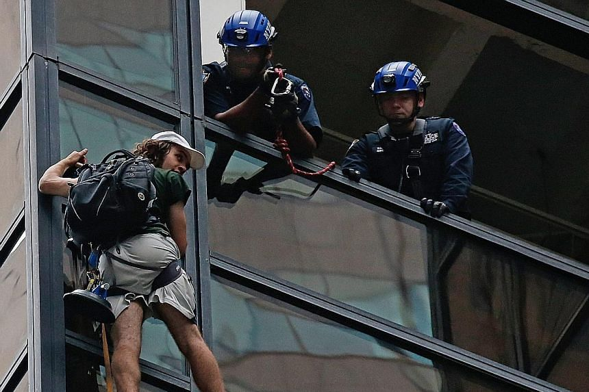Police officers communicating with the climber (left) who made his ascent up Trump Tower using suction cups. Some three hours after his ascent, they managed to grab him (below) and pull him to safety (right).