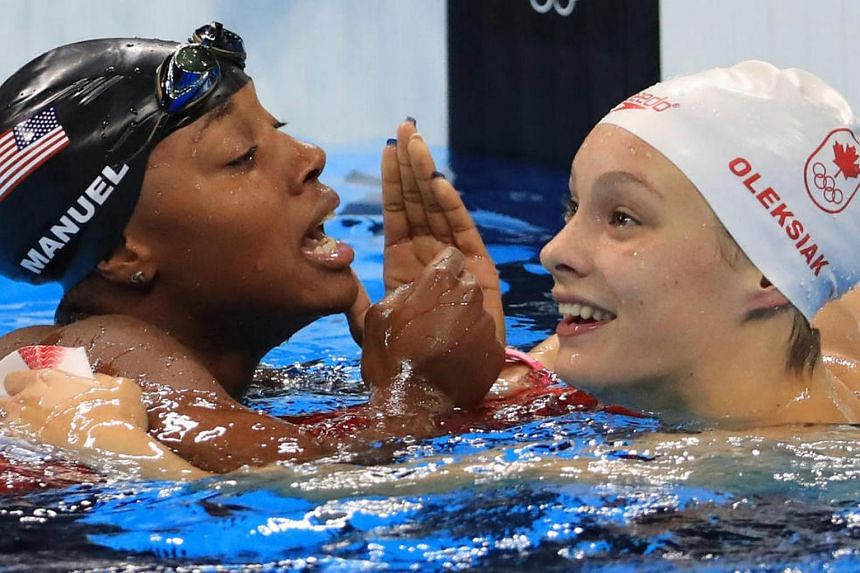 Simone Manuel of USA and Penelope Oleksiak of Canada celebrate winning joint gold medals in the women's 100m freestyle on Aug 11.