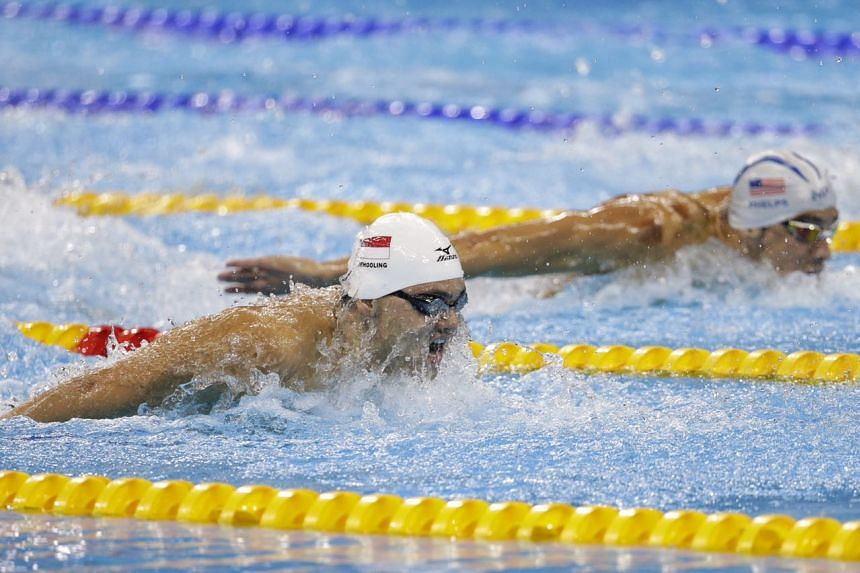Singapore's Joseph Schooling (left) and the US' Michael Phelps take part in the 100m butterfly heats.