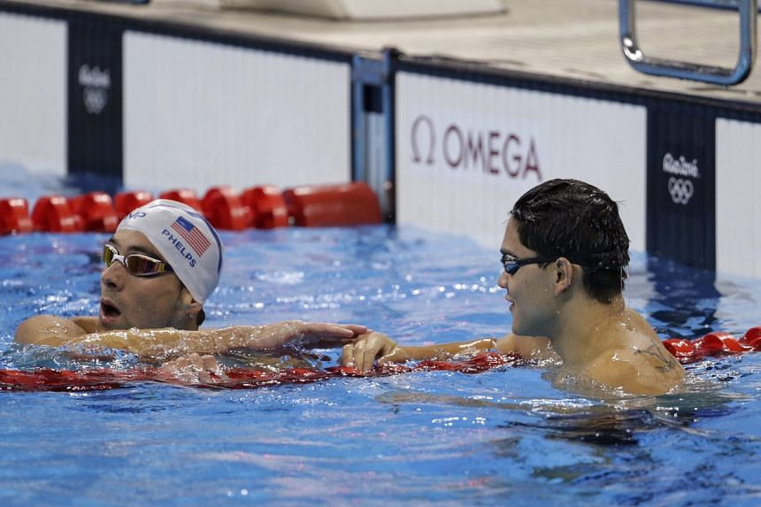 Phelps (left) gives Schooling a congratulatory tap on the hand.