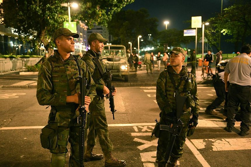 Members of Brazil's armed forces stand on duty as bomb disposal equipment is packed away following a controlled explosion in the Copacabana district of Rio de Janeiro on Aug 9.