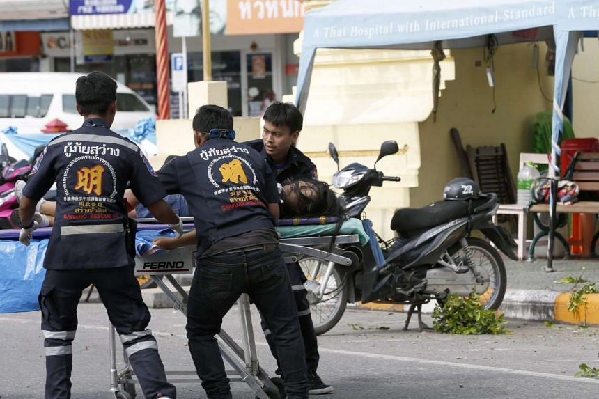 An injured bomb victim lies on the ground as a Thai police officer secures the area following a bomb attack at the city clock tower in the center of Hua Hin, Thailand on Aug 12.