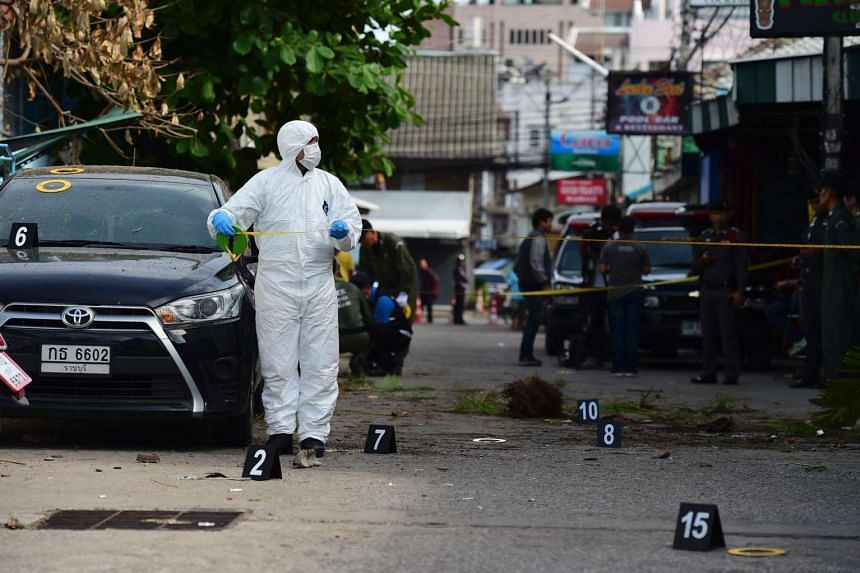 An investigation official collects evidence from the crime scene after a small bomb exploded in Hua Hin on Aug 12.
