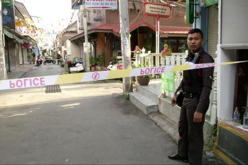 A policeman is seen at the site of one of two bomb blasts which occurred on Aug 11 in Thailand.