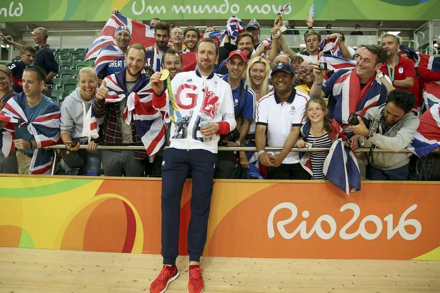 Bradley Wiggins of Britain holds his gold medal and poses with supporters at the 2016 Rio Olympics on Aug 12.