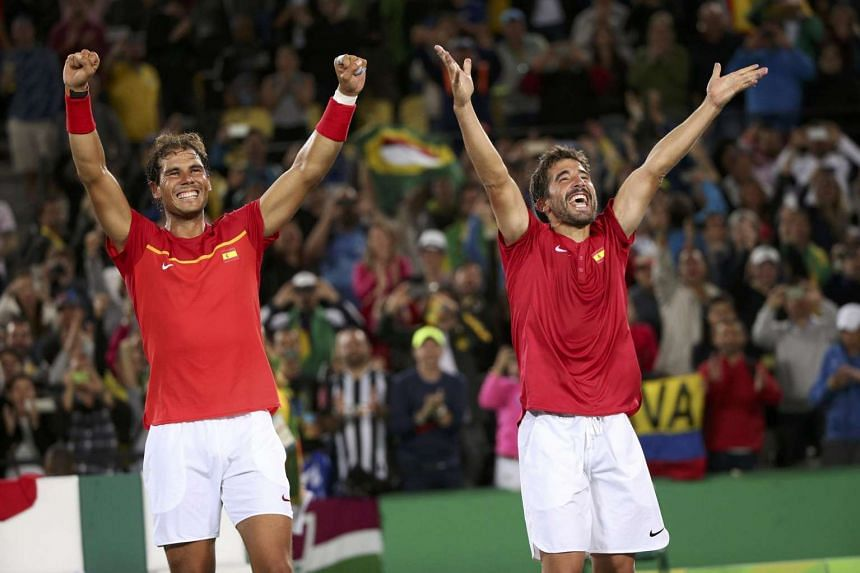 Rafael Nadal of Spain and Marc Lopez of Spain celebrate after winning their match against Florin Mergea of Romania and Horia Tecau of Romania on Aug 12.