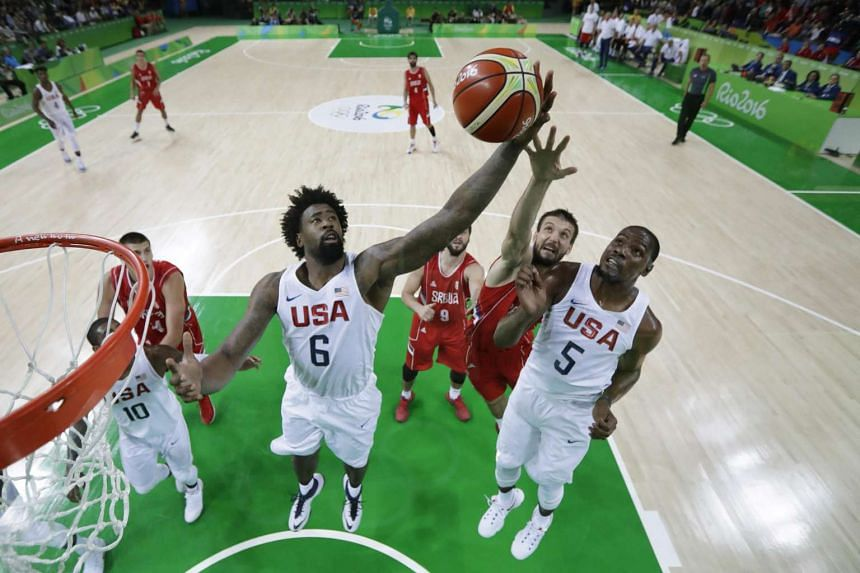 USA's centre DeAndre Jordan (left), USA's guard Kevin Durant and Serbia's forward Nikola Kalinic (2nd right) go for the ball during a men's round group A basketball match between USA and Serbia on Aug 12.