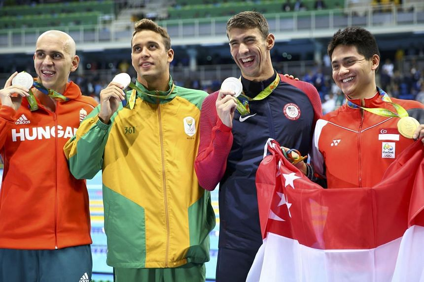 Gold medallist Joseph Schooling holds the national flag while posing with joint silver medallists Michael Phelps of USA, Chad Le Clos of South Africa and Laszlo Cseh of Hungary.