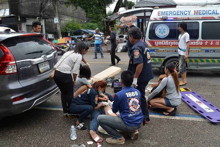 PHUKET: Forensic officers inspecting the scene of the explosion near Patong beach yesterday. The bombs used were hidden in public places and detonated by mobile phones. TRANG: First-aid workers helping those hurt in the blast on Thursday. The wave of